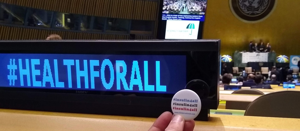 an insulin4all button is held up next to the hashtag healthforall at the UHC Hearing in the UN